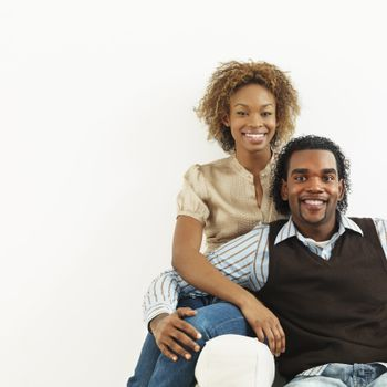 Portrait of smiling happy young couple sitting close together.