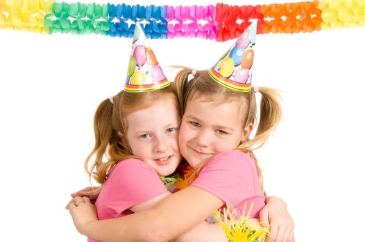 Young twins celebrating their birthday on white