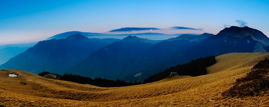 Beautiful panorama mountain landscape with golden grassland in morning.