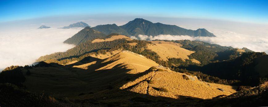 Beautiful panorama mountain landscape with golden grassland .