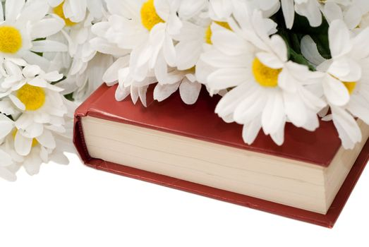 Closeup view of a romance novel with some fake daisies sitting on top, isolated against a white background