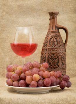 Ceramic bottle, goblet and grapes