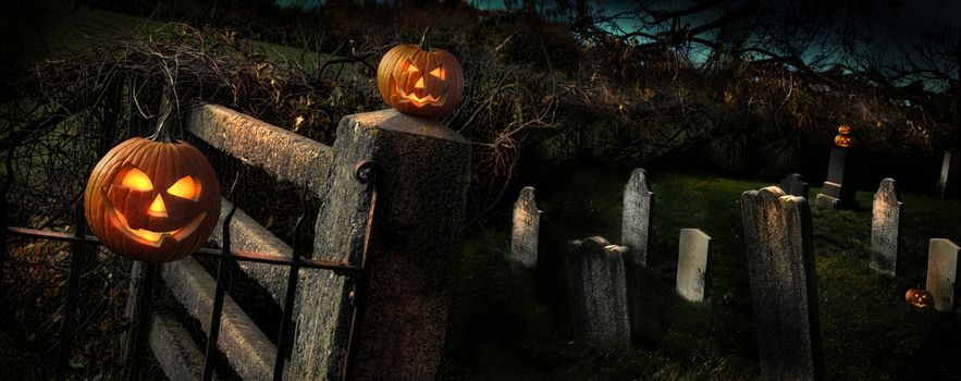 Two Halloween pumpkins sitting on a fence