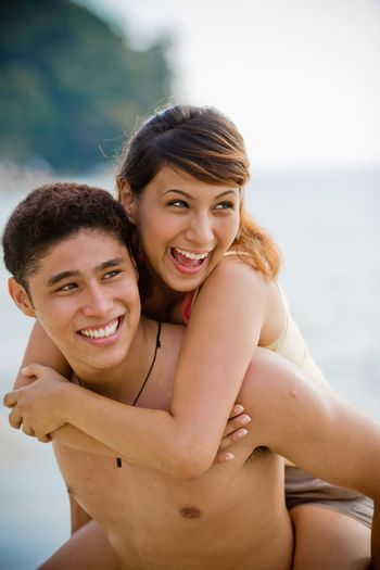 couple having fun carrying piggyback at the beach