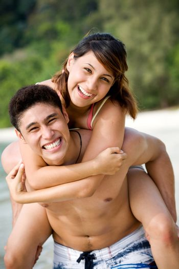 couple having fun at the beach by piggyback carrying