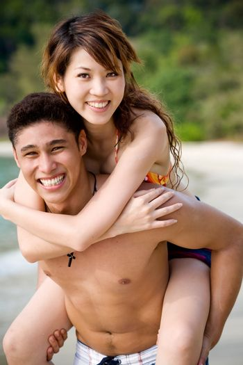 young couple on vacation having fun at the beach