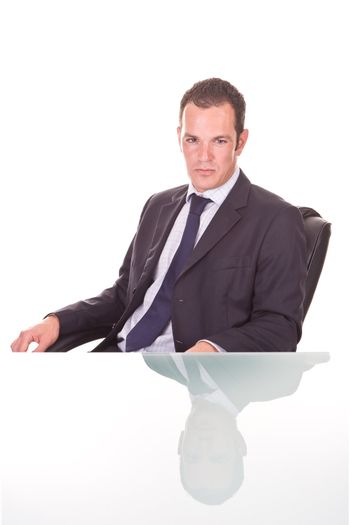 Handsome young confident businessman. On a glass desk, Isolated on white.