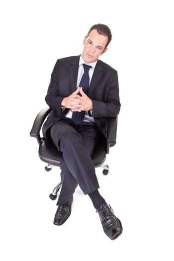 A young businessman, sitting on an office chair, with hands crossed.