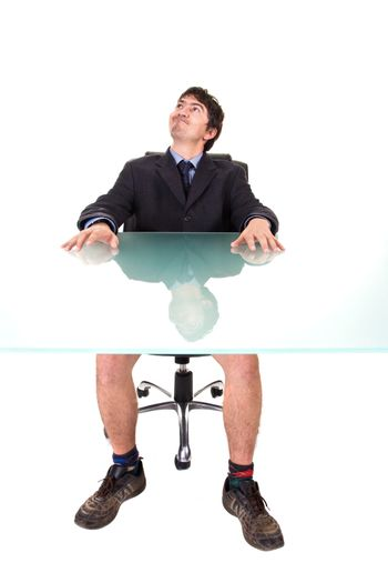 Humorous concept: A businessman, on a suit, sitting on his desk, without pants.