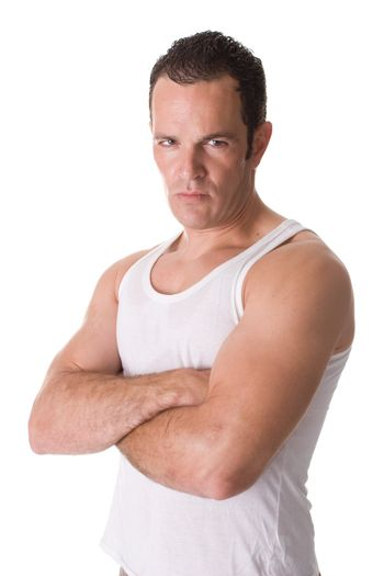 A handsome young man after working out, wearing a sleeveless shirt, standing with his arms crossed.