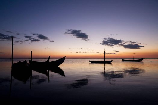 Photo of boats silhouettes by the shore, at sunset.
