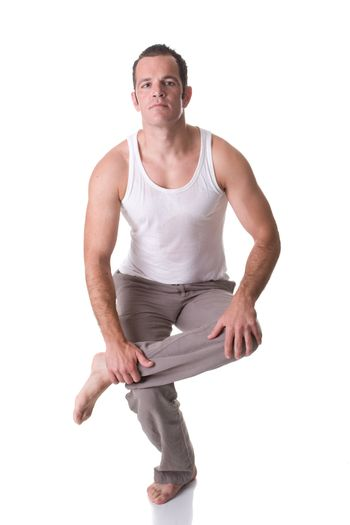 A fit young man doing relaxation and stretching exercise. Isolated on white background.