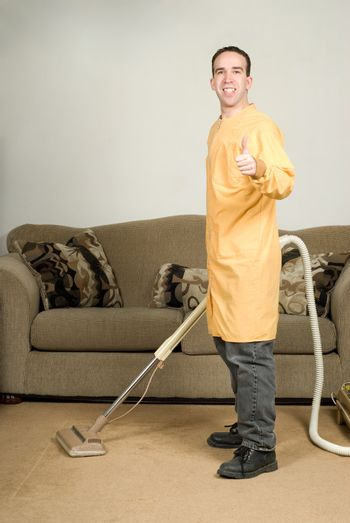A happy worker cleaning the carpets and giving the camera a thumbs up