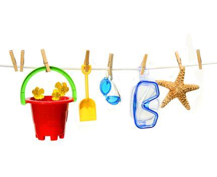 Child's summer toys on clothesline against white