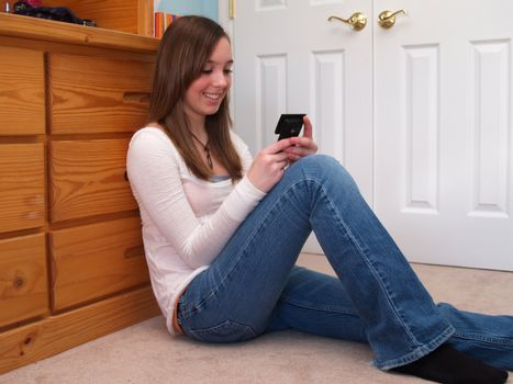 teenage girl, sitting on a floor, texting on a cell phone