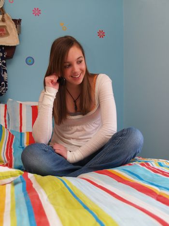 teenage girl, sitting on a bed, talking on a cell phone