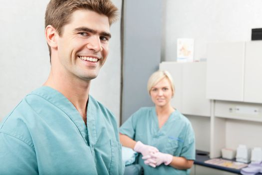 Portrait of male dentist with female assistant standing at dental clinic