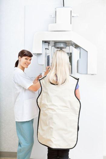 Young female orthodontist taking a panoramic digital xray of a patient`s teeth