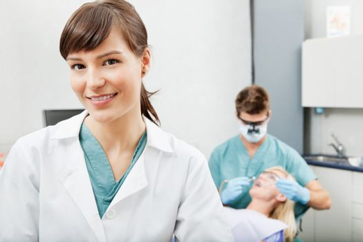 Portrait of a dental assistant smiling with dentistry work in the background