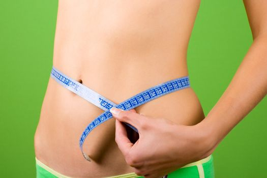 young woman measuring her slim body