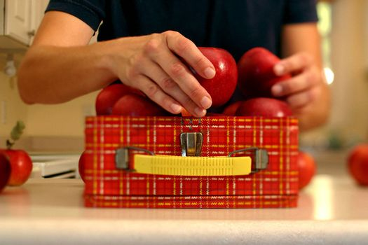 A women is filling a lunch box with apples