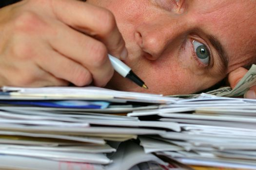 Closeup of person laying on a pile of letters and bills