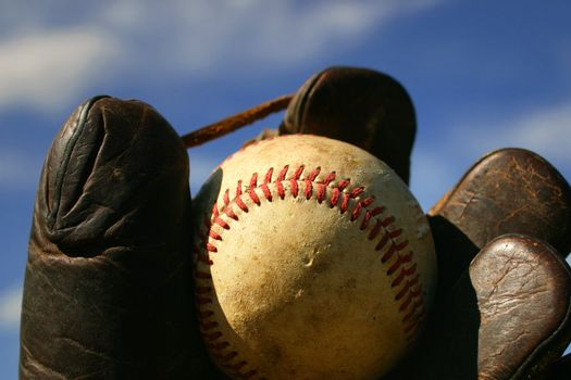 An old baseball in an antique catchers mitt