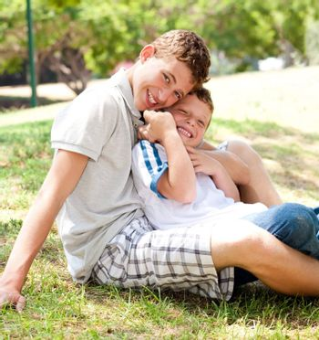 portrait of brothers sitting together on grass in a park