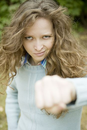 Portrait of an attractive young aggressive female punching