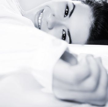 Beautiful young women lying on the bed and smilling