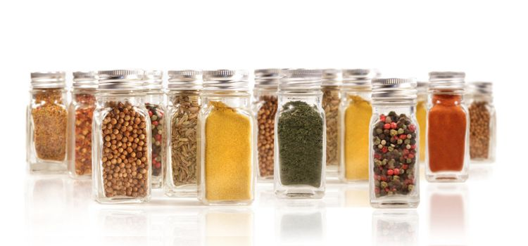 Assorted spice bottles isolated on white