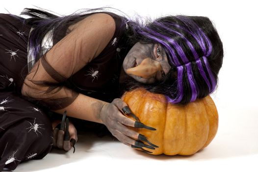 girl dressed up as a witch sleeping on a pumpkin