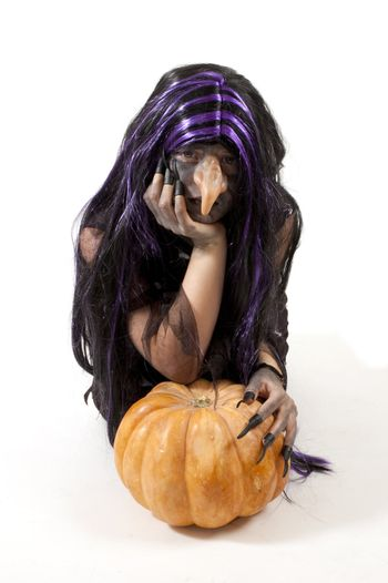 girl dressed up as a witch leaning on a pumpkin