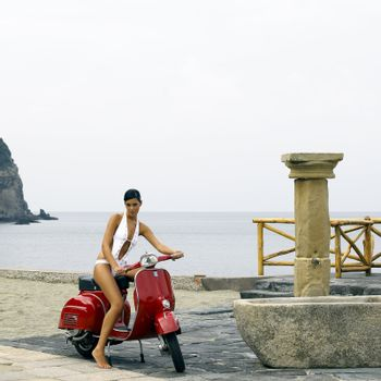 Beautiful woman on a scooter near a beach
