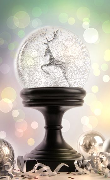 Snow-globe with ornaments against colored background