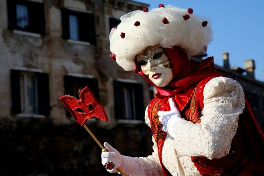 A masked woman with a red eye mask