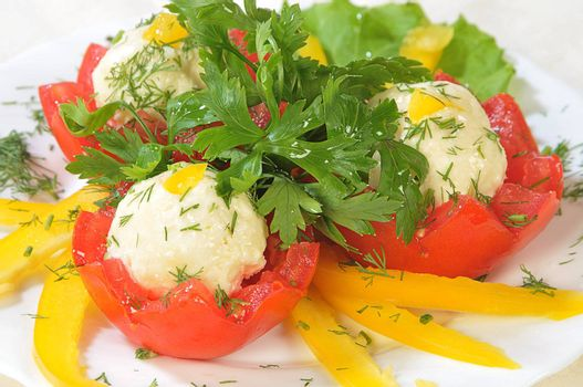 cold appetizer from red tomatoes with cheese marbles on a dish with cutting from yellow paprika and parsley