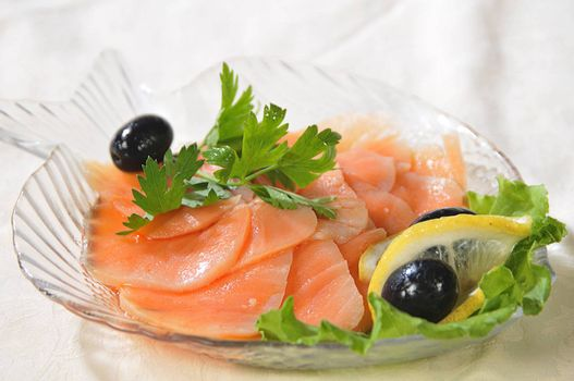 slices are filets of red fish, decorated a lemon, greenery and black olives