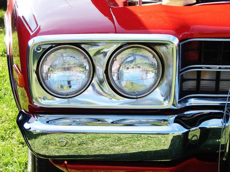Head lights and chrome bumper of a bright red muscle car