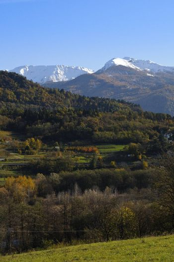 Autumn colors on the hills in the countryside and snow in the distant mountains in the background