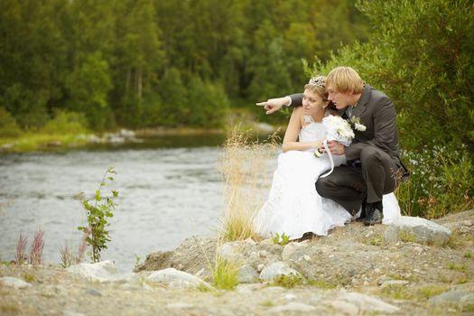 Bride and groom sit on riverbank