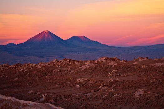 sunset over volcanoes Licancabur and Juriques and Valle de la Luna, Atacama desert, Chile