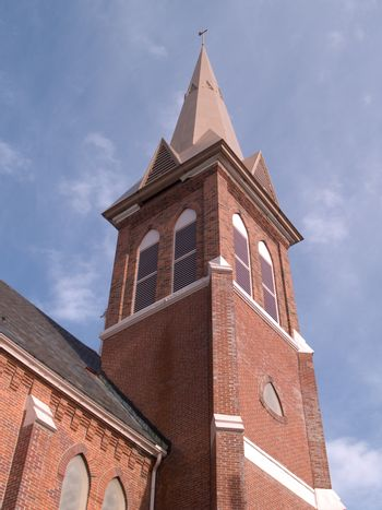 a steeple on a red brick church with blue sky in the background
