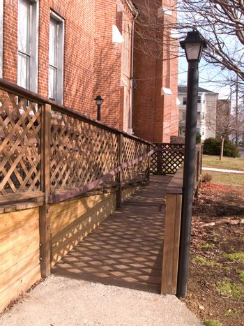an outside handicap ramp by a red brick building