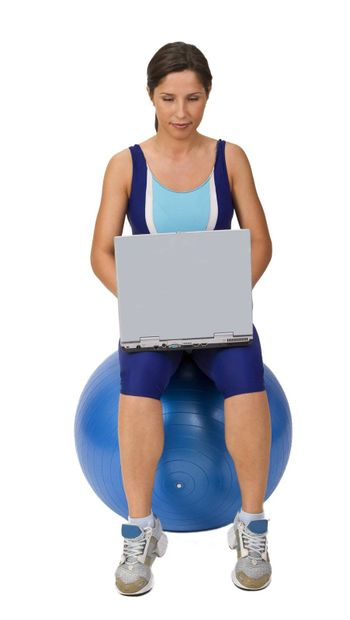 Active young woman using a laptop while sitting on a gym ball.Shot with Canon 70-200mm f/2.8L IS USM