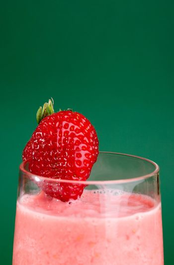 A fresh summer strawberry drink isolated on green