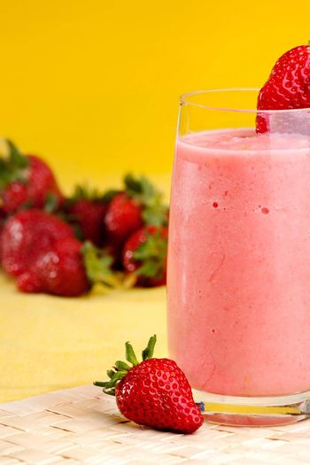 A fresh summer strawberry drink isolated on yellow