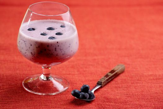 A delicious blueberry smoothie over a red cloth background