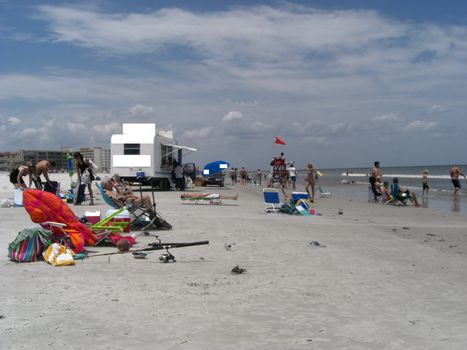 People are all over the beach relaxing while some are swimming in the ocean on a somewhat cloudy day.
