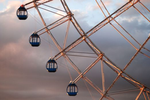Close up of section of Ferris Wheel. four gondolas against cloudy sky